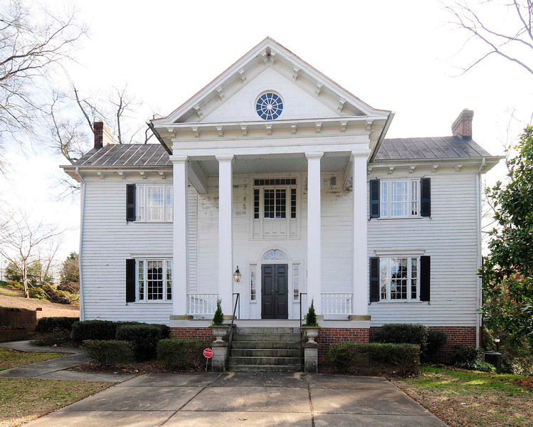 Josiah Kilgore House<br /> <br /> (Lewis House) Built ca. 1838 of heart pine, the Josiah Kilgore House is one of the oldest structures in Greenville County. Architecturally it is an example of the application of the Palladian or Classical Revival style to what is otherwise an upcountry farmhouse. The Palladian style found in the Josiah Kilgore House is more sophisticated than the vernacular styles usually found in this area of South Carolina during the first half of the nineteenth century. The Palladian stance of the square giant-order posts supporting the portico is echoed not only in the entrance but also in the windows at the front elevation and in some of the windows in the rear. The portico is capped by a pediment of plain design with an oculus. The bracketing of the pediment and eaves is a later addition. The house is a two-story L-shaped design on a low foundation. Shiplap is used in the protected areas under the porches while the remainder of the exterior is clapboard. The rear elevation with projecting rear wing has a three-bay porch on the right side of the wing balanced by a similarly gabled enclosed porch on the left. Originally located in a commercial area of downtown Greenville adjacent to Buncombe Street Methodist Church, the structure was moved to a five acre site in McPherson Park to prevent its demolition. Listed in the National Register April 28, 1975.