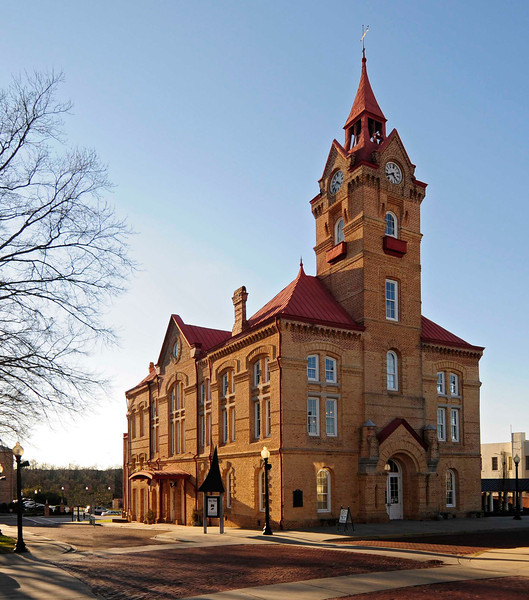 """Newberry Opera House<br /> <br /> Located on a lot where John Leavell, among others, operated a tavern in the town's earlier years, the ca. 1881 Newberry Opera House became a popular cultural center from the time of its dedication in 1882. Presented at the opera house were stage dramas, operas and operettas, minstrel shows, musical comedies and similar attractions which toured the country and were major features of the town's cultural and social life. With the advent of movies, and the building of larger auditoriums in the city, the Opera House was used exclusively as a movie theater. The Newberry Opera House building is Romanesque Revival in design, with a tall steeple and a wide gable on the front side. Its bricks were handmade in Newberry. The parcade is sloping. The balcony is wide and also sloping. The building was, """"in all likelihood, designed out of a pattern book, and shows the influence of Philadelphia architect Frank Furness."""" Located on Newberry's central square, the old building was the hub of cultural and civic activities for many years. Listed in the National Register December 2, 1969."""