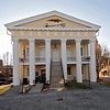 Old Court House<br /> <br /> The Old Court House, erected 1852, was designed by Jacob Graves and built by James Damron. An outstanding example of Greek Revival architecture in stuccoed brick, the building has six fluted, Tuscan columns which support a massive, triangular pediment. The intricate Doric entablature includes a frieze design of alternating triglyphs and undecorated metopes and regulas of architrave and mutules of cornice decorated with guttae. The building's elaborate detail and massive proportions attest to the affluence of pre-Civil War Newberry County. During Reconstruction, Osborne Wells was assigned the task of remodeling the courthouse. Wells' additions included two-column porticos at side entrances and a bas-relief mounted on the frontal pediment. This bas-relief depicts the spirit of the prostrate state: a U.S. eagle holds an uprooted palmetto tree in its talons; perched upon the tree roots is a gamecock crowing defiantly; at the top of the tree a dove bears an olive branch. This building, the fourth in a series of five County Courthouses, was used for court sessions between 1852 and 1906. Listed in the National Register August 19, 1971.
