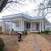 "Hagood-Mauldin<br /> <br /> The Hagood-Mauldin House is significant for its architecture and for its association with James Earle Hagood and Judge Thomas J. Mauldin. The earliest section of the one-story frame house was built ca. 1856 in the town of Old Pickens Court House. The first owner, James Earle Hagood was a public official, lawyer, and planter of Pickens District. When Pickens District was divided into Oconee County and Pickens County in 1868, the house was disassembled, each board and beam was carefully numbered, and it was loaded onto wagons and reconstructed at its present site in the ""new"" town of Pickens. The original house was constructed using log beams and joists at the floor and attic, each carefully cut, fitted, and pegged. It is believed that Mr. Hagood made additions to the house shortly after 1868 and later in 1886. Judge Thomas J. Mauldin expanded the front porch to a Classical Revival style in 1904 and also added, just to the south of the house, a smaller Classical Revival style building that he used as his law office. Listed in the National Register October 9, 1997."