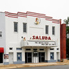Saluda Theater<br /> <br /> Designed by Charles B. Thompson, the Saluda Theatre is a two-story, stuccoed masonry building constructed in 1936 as a cinema. The Saluda is significant as an unusually intact example of a small town theatre in the Art Deco style and for its role as a focal point for entertainment in the community during the 1930s and 1940s. The theatre reflects a period of motion picture theatre construction that swept the country in the 1920s and 1930s. Like most other movie theatres constructed during the second decade of the period, the building was influenced by the Art Deco style. The crisp, simple lines of the façade and the geometric designs of the interior wall finishes and lighting fixtures reveal the influence of the Art Deco style. The theatre is prominently sited in downtown Saluda across the street from the courthouse square. It was open for forty-five years, closing in 1981. Listed in the National Register December 13, 1993.
