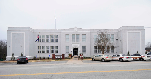 "Woodruff High School<br /> <br /> Woodruff High School is historically significant for its long association with education and civic activity in Woodruff during the first half of the twentieth century, and is also architecturally significant as an outstanding and well-preserved example of the work of prominent Greenville architects Frank H. and Joseph G. Cunningham. Woodruff High School was built in1925 at a cost of $50,000. It replaced the original high school, which was built in 1908 on East Georgia Street. The Cunningham-designed building housed the high school until a new facility constructed outside of downtown opened in September 1953. It subsequently served as the junior high school and, in the late 1960s, was home to the elementary school. In 1978 the City of Woodruff acquired old Woodruff High School and adapted it for use as its city hall and police headquarters. The two-story building's form is a modified ""H"" plan with a three-part center section, two perpendicular wings, and a flat roof. It occupies nearly 30,000 square feet, including a 600-seat auditorium. Exterior masonry walls are covered in gray stucco. The modern windows are a metal awning variety. Moldings and Gothic arches ornament the exterior, particularly at the entrances. Woodruff High School exhibits many of the defining decorative characteristics of the collegiate Gothic style. Popularized after the First World War, the collegiate Gothic style was noted for recessed entrances framed by pointed arches. Other defining elements include brick exterior walls with raised moldings, large window bays with multi-paned sashes, and a flat roof with parapet. Woodruff High School, as originally built, exhibited all of these features, plus small quoin-stones, drip moldings with bosses and a tablet molding at the main entrance. Listed in the National Register October 18, 2006."
