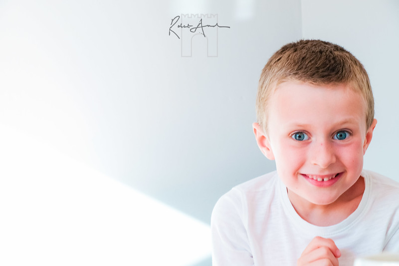 Anice clean light and airy white background focusses the viewer on the suject - the kind, caring brother.