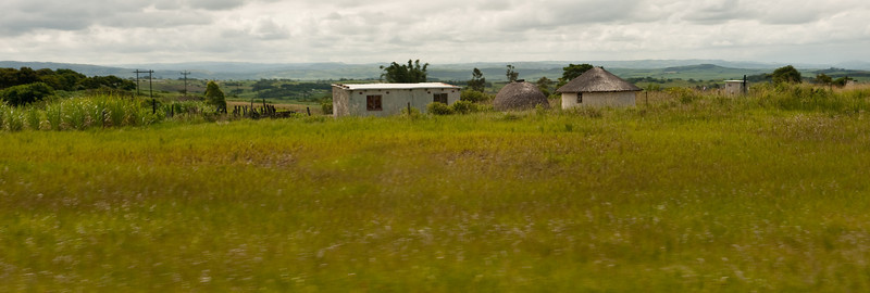 Modern square house with rondavel, beehive hut, and outhouse.  A combination we see In the rural areas throughout South Africa and Swaziland.