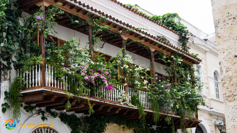 Intricate wooden balcony covered in flowers above a Cartagena street.