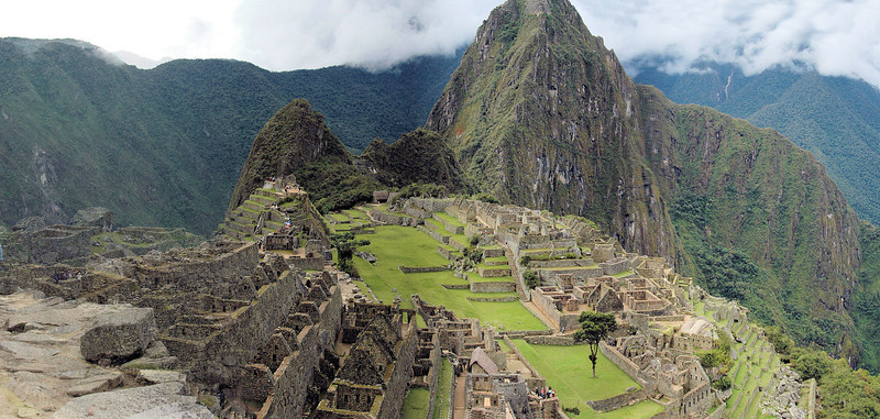 "Machu Picchu ( ""Old Peak"") is a pre-Columbian 15th-century Inca site located 7,970 ft above sea level. It is situated on a mountain ridge above the Urubamba Valley in Peru, which is 50 miles northwest of Cusco and through which the Urubamba River flows. Most archaeologists believe that Machu Picchu was built as an estate for the Inca emperor Pachacuti (1438–1472)."