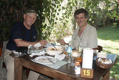 """That's me and Alec Earnshaw at the dining table for lunch.  We are going over a check list of birds seen that morning.  It totaled over 75.  I met Alec over the internet. He offered his services as a guide for a day and we accepted.  Alec picked up my wife and me and took us to Reserva Natural Otamendi.  Otamendi is northwest of Buenos Aires.  It is a nature reserve  on the Parana de las Palmas river.  For the next five hours I saw and photographed countless number of """"lifer"""" birds. Alec uses an Mp3 player loaded with South American bird songs.  He has a custom built speaker with a volumn control that straps to his waist.  The bird songs brought in reluctant birds and birds that were in heavy cover.   We broke for lunch and drove to a restaurant which looked like an old brick factory.  As we entered the restaurant we were escorted to the backyard to vine covered tables. Lunch was a typical Argentinan country meal of beef, chicken, pasta, vegetables and bread.  The birding was very good that morning and the food even better. However, the best part about the day were the people we met and their warm reception of us.  Alec can be contacted at  http://www.fotosaves.com.ar/Lugares.html for day guide trips."""