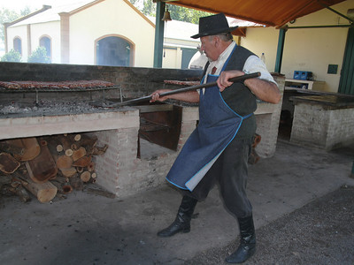 Coals from a wood fire were picked up with a shovel and placed under the meat.