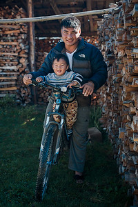 Father and son on a bicycle at a farm in the Phobjikha Valley