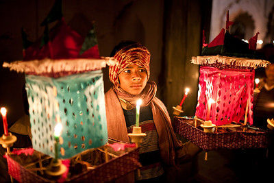 A young boy carries lanterns while awaiting the beginning of the Mehndi procession.