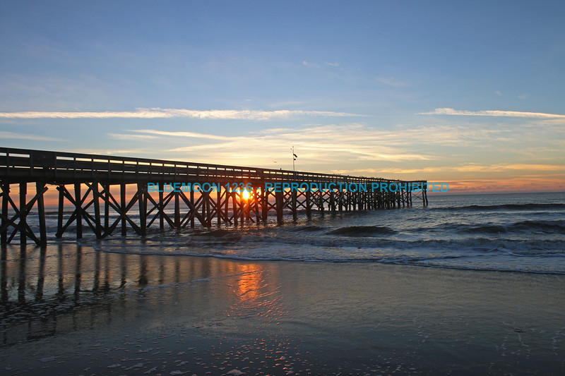 Sun is rising on ocean behind fishing pier at Isle of Palms, SC with brilliant colors and wispy clouds Rocky, mountainous shoreline meets emerald green waters with bright blue sky in background.  bluemoon1236; www.bluemoon1236.smugmug.com