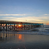 "Sun is rising on ocean behind fishing pier at Isle of Palms, SC with brilliant colors and wispy clouds Rocky, mountainous shoreline meets emerald green waters with bright blue sky in background.  bluemoon1236;  <a href=""http://www.bluemoon1236.smugmug.com"">http://www.bluemoon1236.smugmug.com</a> ,Bluemoon Fine Photography"