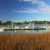 Boats docked at a marina on the intracoastal waterway in South Carolina with blue sky, wispy white clouds and marsh grass.  Bluemoon1236