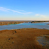 "Marsh in the winter in the tidal waters of the intracoastal waterway in Isle of Palms South Carolina.  It is high tide and early morning light with blue sky and wispy clouds in background. Rocky, mountainous shoreline meets emerald green waters with bright blue sky in background bluemoon1236;  <a href=""http://www.bluemoon1236.smugmug.com"">http://www.bluemoon1236.smugmug.com</a> ,Bluemoon Fine Photography"