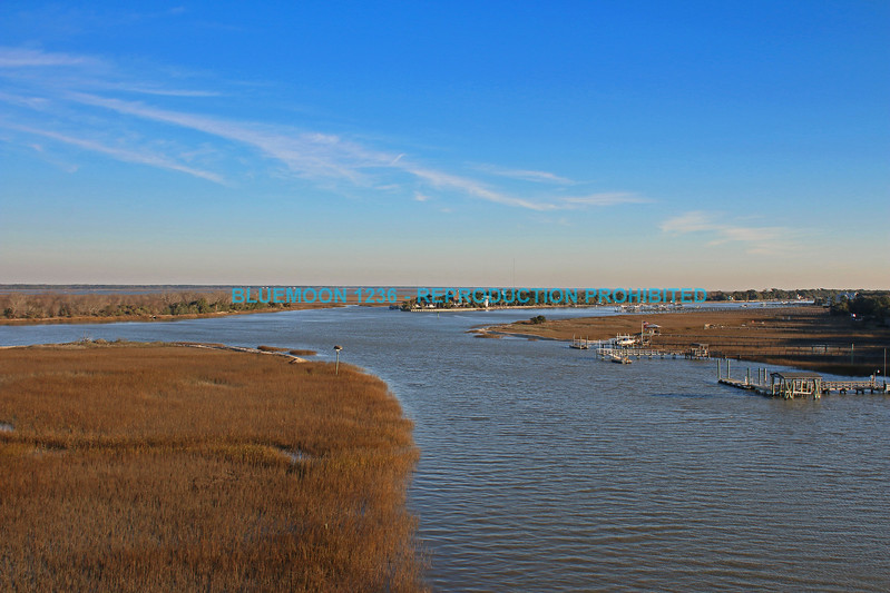 Marsh in the winter in the tidal waters of the intracoastal waterway in Isle of Palms South Carolina.  It is high tide and early morning light with blue sky and wispy clouds in background. bluemoon1236; www.bluemoon1236.smugmug.com