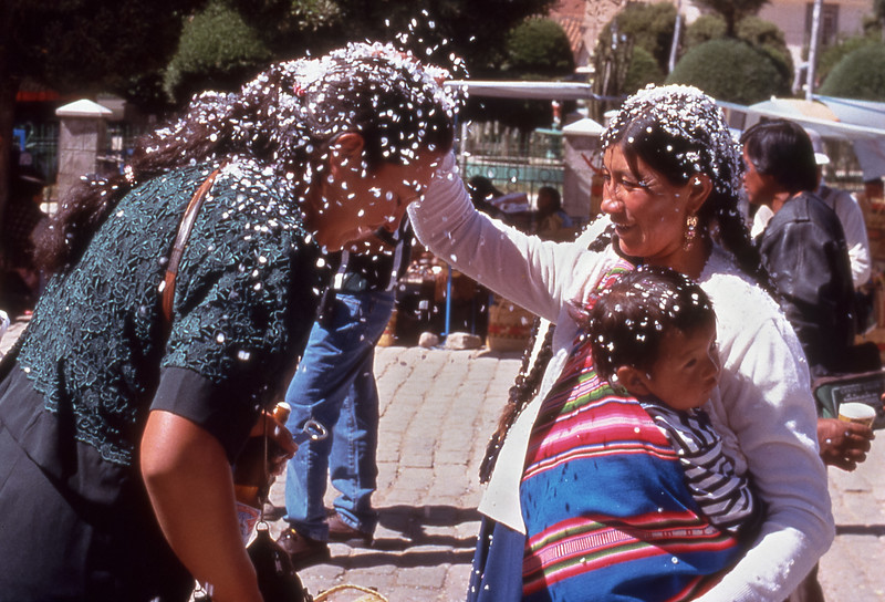 Women cover each other in confetti after vehicle blessing  in Copacabana, Bolivia.