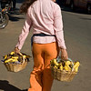 Young woman carries baskets of bananas, Villarica, Paraguay