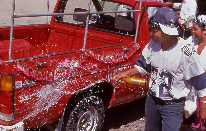 Man sprays truck w/ beer after vehicle blessing by Catholic priest, Copacabana, Bolivia.