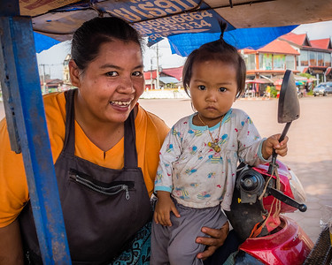 A street vendor and her daughter outside a temple in Vientiene, Laos