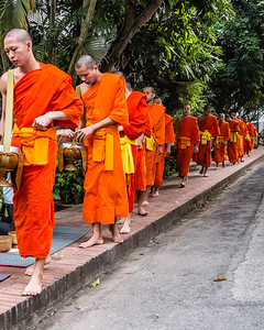 Dawn procession of monks from the monasteries in Luang Prabang collecting food for their day