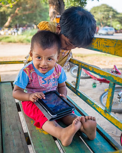 A boy and his sister play on an IPad in Bagan, Myanmar