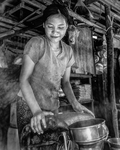 .  A young women pours cooking oil.