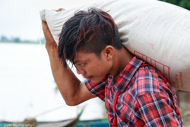 A man carries a bag of rice for famiies in need.