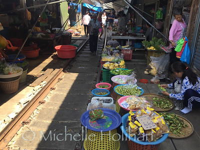 MAE KLONG, THAILAND - NOVEMBER 5, 2018: Unidentified vendors sell produce and spices at the Mae Klong Railway Market.