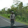 Cop coming for his bribe at police roadblock. Bali Highlands, Indonesia