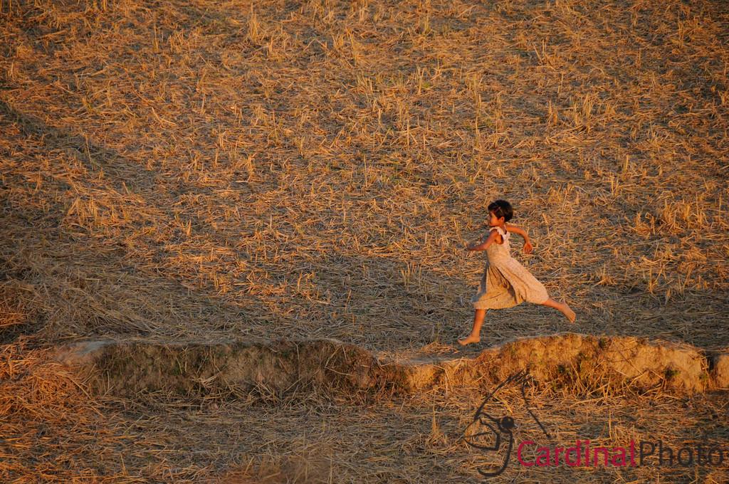 Young Burmese Girl running across a rice paddy field near Mrauk U, Rakhine Division, Arakhan Kingdom, Myanmar, Burma, Southeast Asia