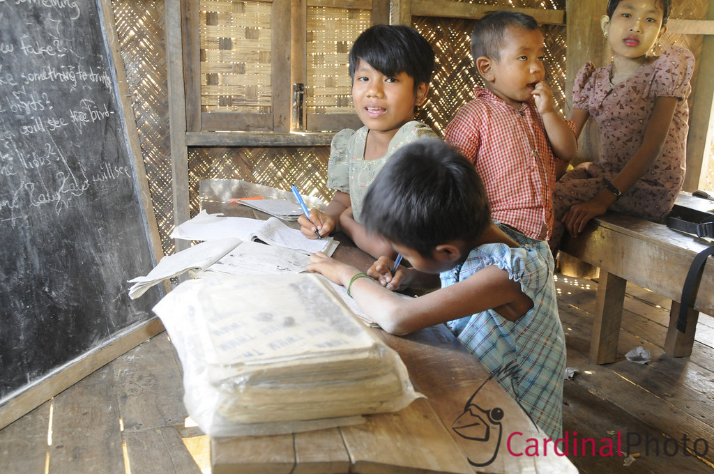 Chin children studying on their holiday at their local school, built by eco-tourist donations. Their teacher, a university graduate who could not find a job in the city teaches the one-room school for $10/month. The Chin are one of the oppressed minorities in Burma. Chin Villages near Mrauk U, Rakhine State, (Arakhan Kingdom), Myanmar, Burma, Southeast Asia