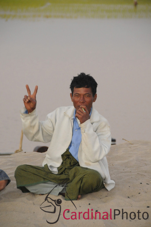 Peasant fisherman smoking and waving  in a transient village after returning back from a day of fishing, in the Irrawaddy River near Bagan, Plain of Temples, Myanmar (Burma), Asia