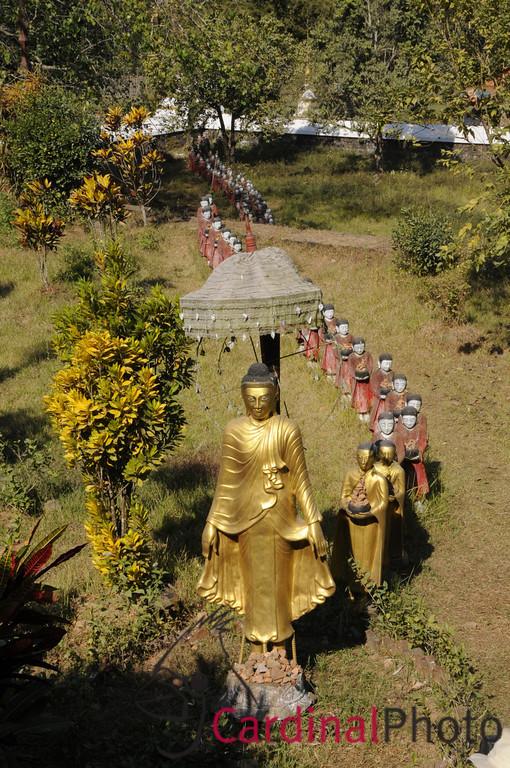 Row of Buddhas and emerging Monk Statues in the garden outside the Mahamuni location near Mrauk U, Rakhine Division, Arakhan Kingdom, Myanmar (Burma), Southeast Asia