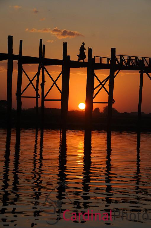 Monk crossing the U Bein Bridge at Sunset in Amarapura near Mandalay, Burma, Myanmar, Southeast Asia