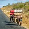 Two men transporting large sacks of charcoal on their bicycles, near Ankororoka, Madagascar