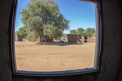 From the inside looking out; a newly renovated schoolhouse serves as an interesting vantage point to observe temporary classrooms made out of logs, mud, and tin.