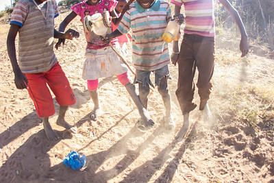 Local children from the village of Mafacitela play a game of soccer in the dust. A wad of plastic bags filled with sand is the only necessary gear.