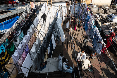 These images show one of the very large outdoor laundries in Mumbai.  The people who work here washing the cities clothes daily also live in small rooms there.  Everyone works, parents and kids.  One of them gave me an inside tour of the place.  It is a mini city with everything you need inside and out.