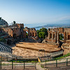 Built in the 3rd century BC, the 10,000 seat ancient Greek Amphitheater in Taormina, Sicily still hosts concerts today. In the background is the coastline along the Ionian Sea.