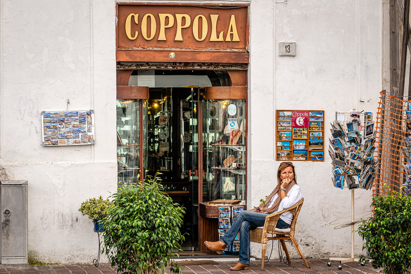 In Naples Italy a woman sits in front of her customerless shop...bored?... frustrated?...or simply lost in thought a world away?