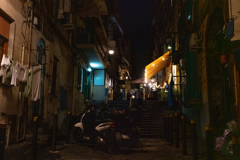 Laundry on the left, trash on the right, outdoor dining at top the steps: tried to capture the combination of eclecticism and grittiness of this night scene in Naples Italy.