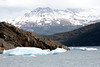 Iceberg floating on Lago Grey near the terminus of Glacier Grey.  Basaltic lava formation in background. Torres del Paine National Park.  Southern Patagonia, Chile.