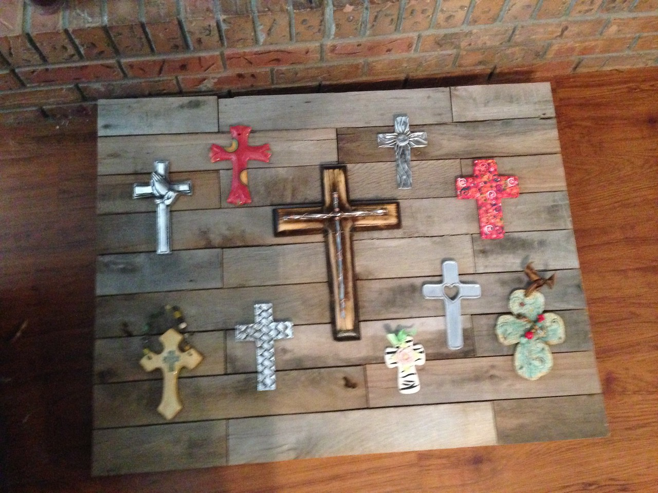 Fireplace cover made from old wooden pallets. My wife has dozens of crosses she collects, so I took a few of them and connected them to the cover using thin wire.