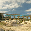 Pont Du Gard aqueduct and bridge crossing a river with boulders and stabilization fencing in the foreground.  The aqueduct is framed by a bright blue sky with puffy and wispy white clouds.  www.bluemoon1236.smugmug.com; bluemoon1236 ,Bluemoon Fine Photography ,Bluemoon Fine Photography