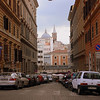 Rome streetscapes : Narrow alleyways crammed with cars and scooters, apartments with long wooden blinds (but no balconies), and the bell towers and cuppolas of churches.