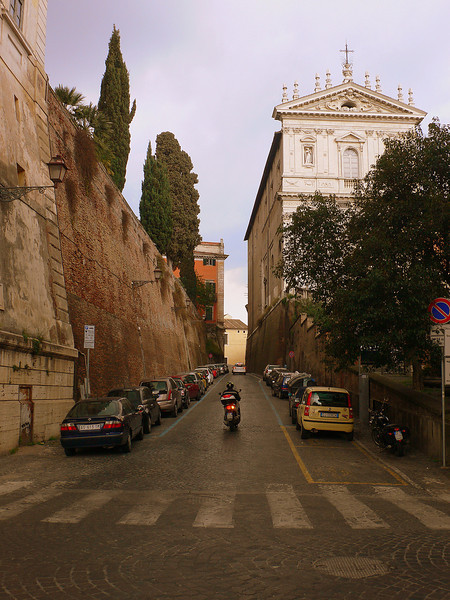 A Roman streetscape : A scurrying scooter, fortified walls, cobbled streets, and the Baroque facade of the Santi Domenico e Sisto, a church whose construction spanned almost a 100 years (from 1569 to 1663).