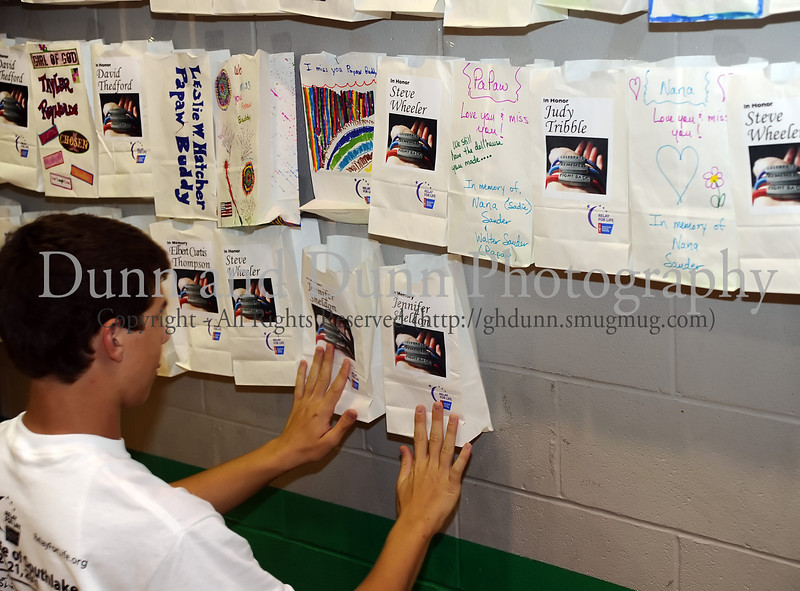 Nathan Tribble pastes luminaries honoring cancer survivors and victims on the wall of the Carroll High School gym at Southlake's second annual Relay for Life/Rachel's Rally fundraising event for the American Cancer Society last Friday night at Carroll High School.