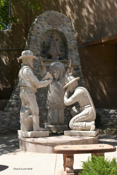 El Santuario de Chimayó, New Mexico - The statue of the Three Cultures Monument, with a Native American, a white settler, and a priest overlooked by the Virgin Mary