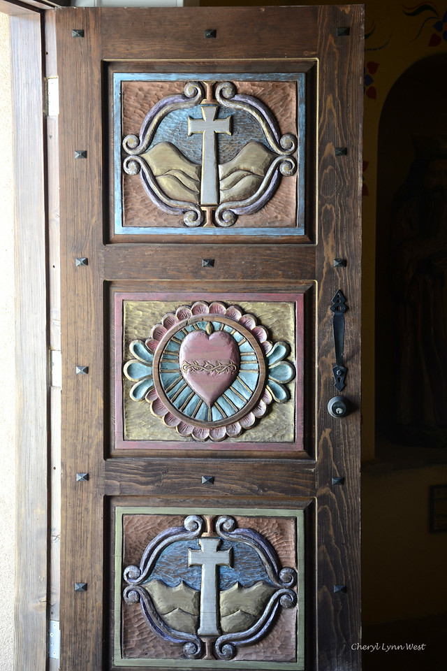 El Santuario de Chimayó, New Mexico - Carved and painted door to  the Santo Niño Chapel