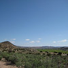 """View from Posi-Ouingue (""""Green-ness"""") Pueblo. This is an unexcavated site, circa 1400-1500. It was three stories high and had up to 1,000 ground floor rooms. It is located on a ridge above the Rio Chamas at Ojo Caliente."""